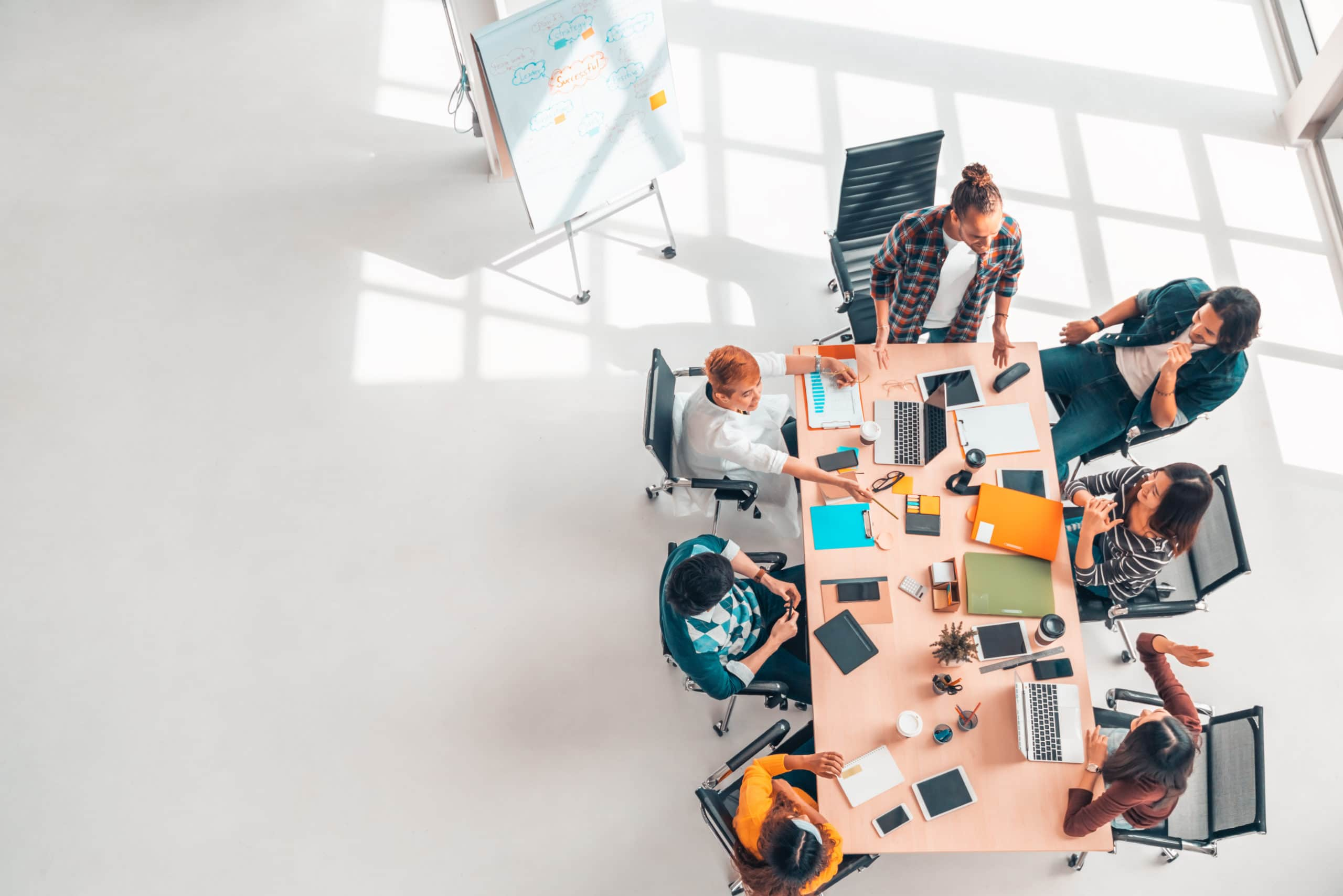 A startup management team having a discussion in an arial view of a table